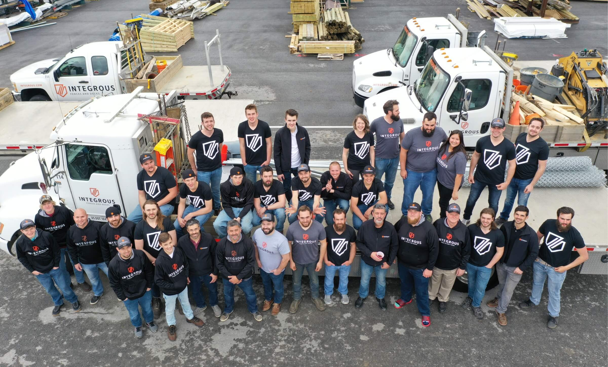 The entire Integrous team posing in front of their large flatbed truck